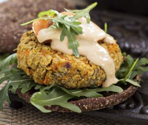 Närbild på en vegetarisk burgare i mörkt bröd med ruccola och sås ovanpå.
